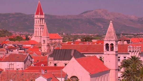 Aerial view of Trojir, Croatia's port and 1000 year old city. People walk along the port. Zoom out. Royalty-free stock video