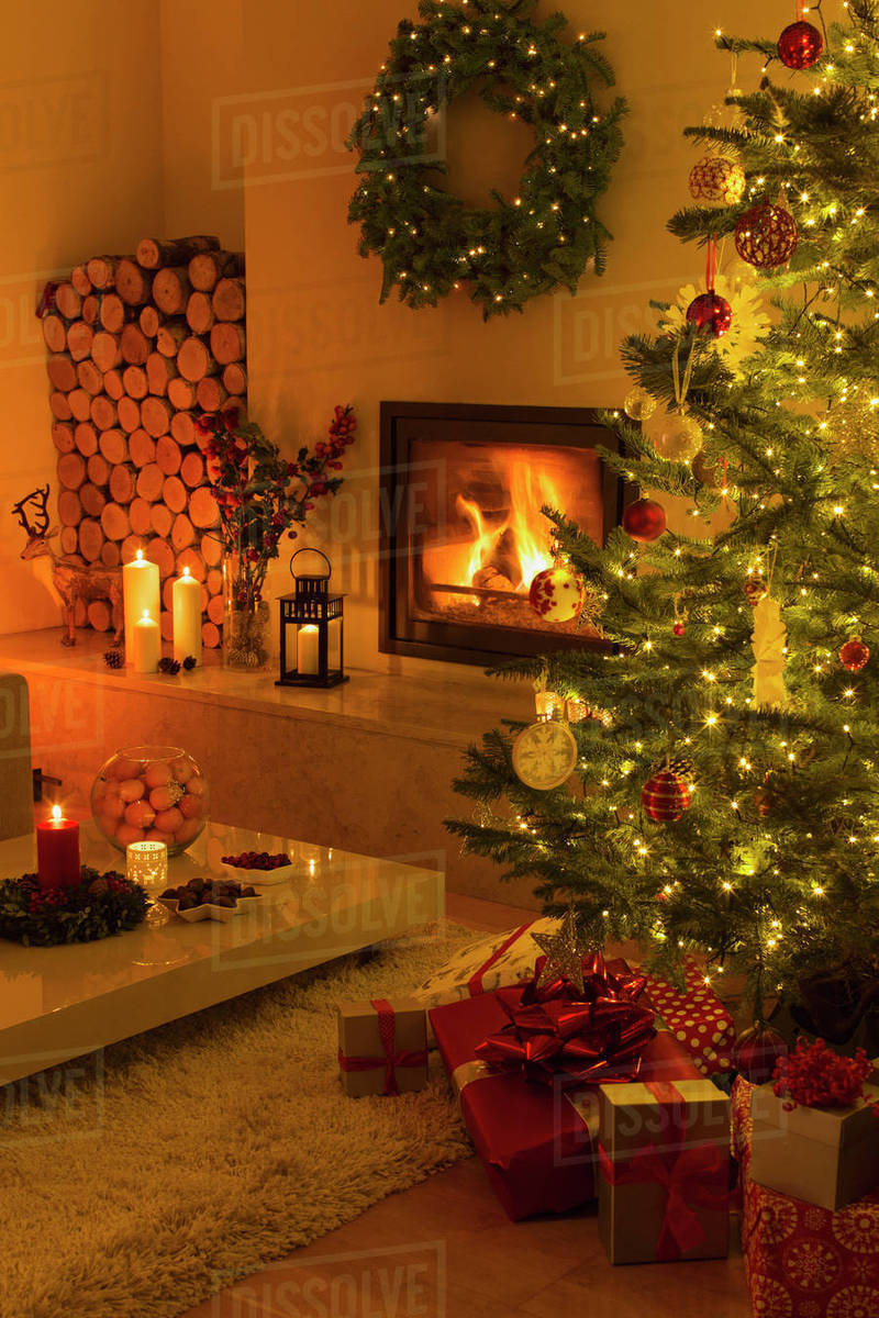 Living Christmas Tree.Ambient Fireplace And Candles Illuminating Living Room With Christmas Tree And Decorations Stock Photo