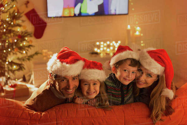 Portrait smiling family wearing Santa hats on living room sofa Royalty-free stock photo