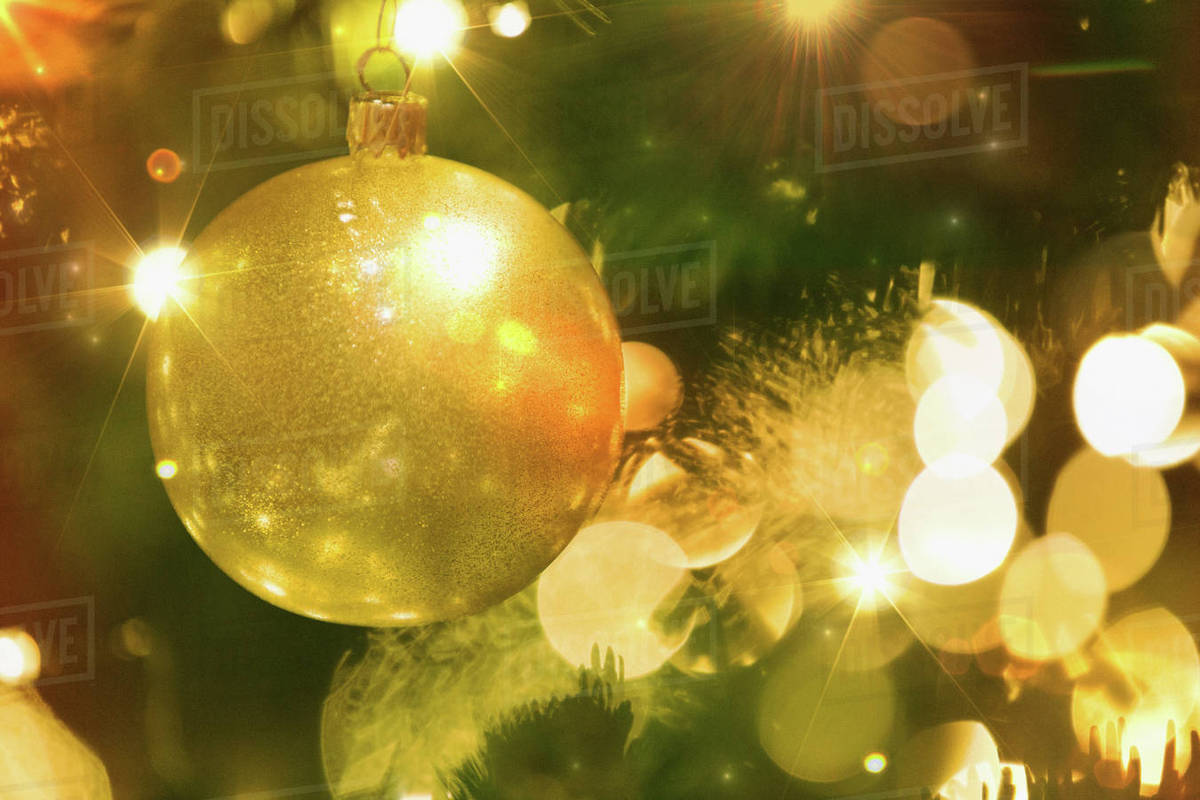 Close Up Golden Ornament And String Lights On Christmas Tree Stock Photo