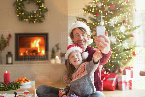Father and daughter in Santa hats taking selfie with camera phone in Christmas living room Royalty-free stock photo