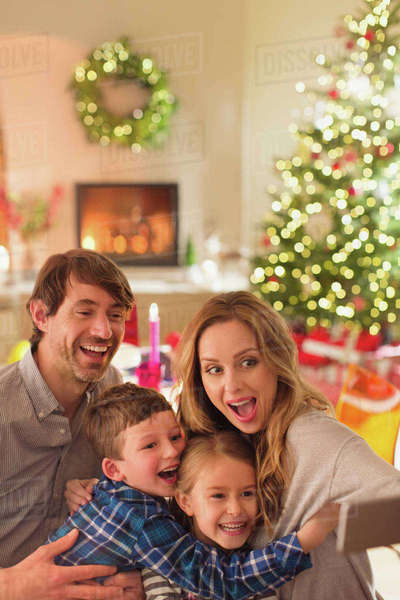 Silly family taking selfie with camera phone in Christmas living room Royalty-free stock photo