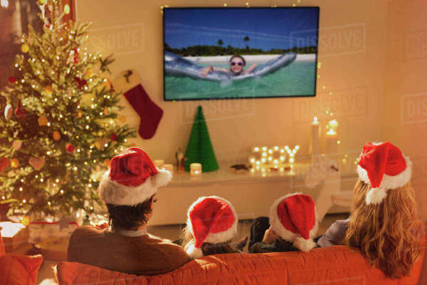 Family in Santa hats watching summer holiday video on TV in Christmas living room Royalty-free stock photo