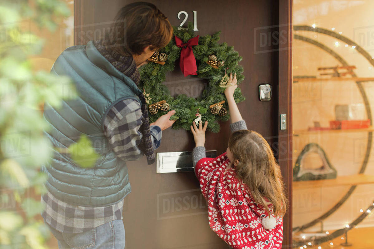 Father And Daughter Hanging Christmas Wreath On Front Door