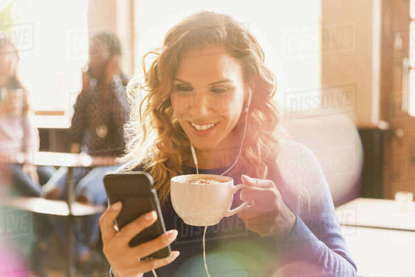 Woman with headphones drinking cappuccino and video chatting in cafe Royalty-free stock photo