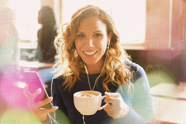 Portrait smiling woman with headphones listening to music on mp3 player and drinking cappuccino in cafe Royalty-free stock photo