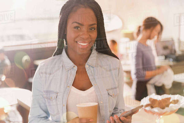 Portrait smiling African woman using cell phone and drinking coffee in cafe Royalty-free stock photo