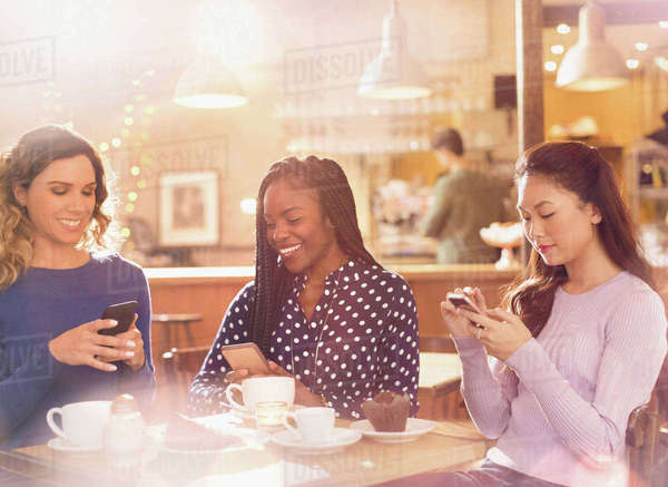 Women friends texting with cell phones at cafe table Royalty-free stock photo