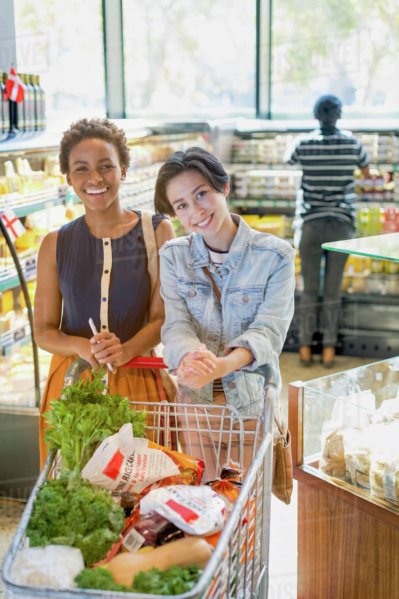 Portrait Young Lesbian Couple With Shopping Cart In Grocery Store Market Stock Photo
