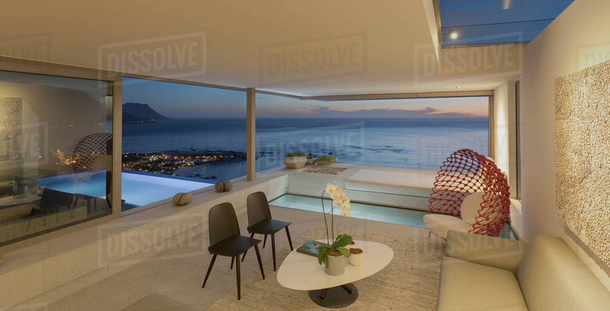 Illuminated Modern, Luxury Home Showcase Living Room And Pool With Twilight  Ocean View