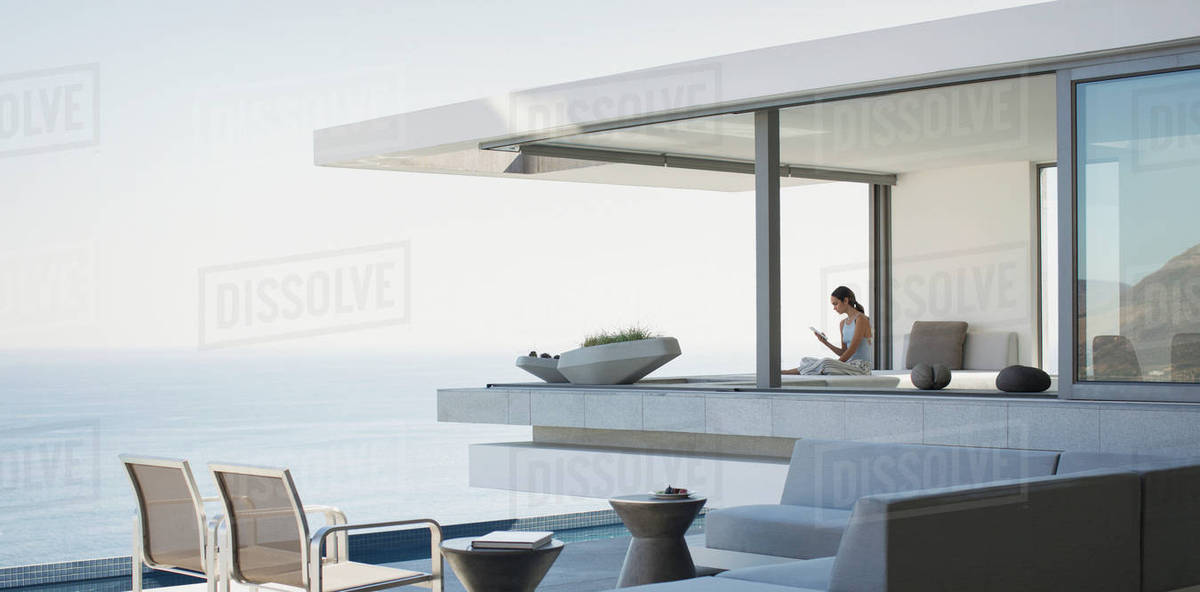 Woman Sitting On Modern, Luxury Home Showcase Exterior Patio With Ocean View