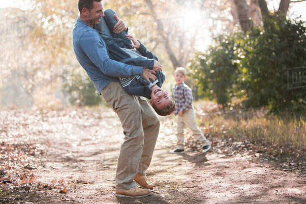 Playful father lifting son upside-down on path in woods Royalty-free stock photo