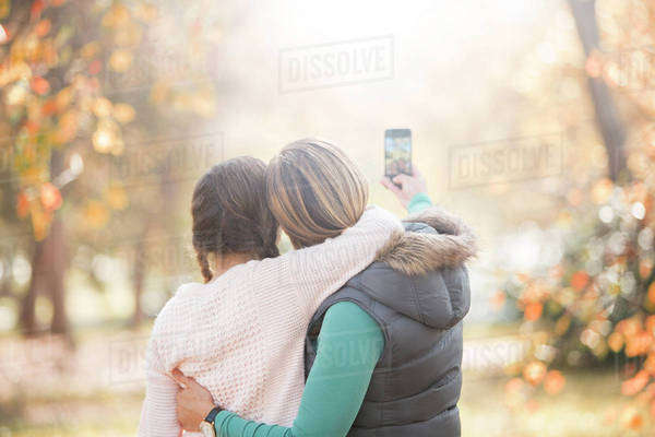 Affectionate mother and daughter taking selfie outdoors Royalty-free stock photo