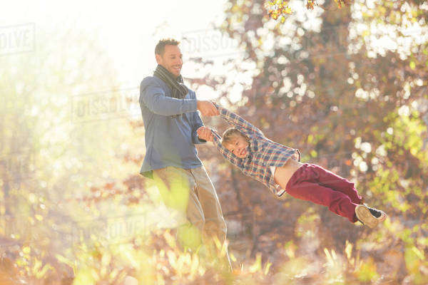 Father spinning son among autumn leaves Royalty-free stock photo