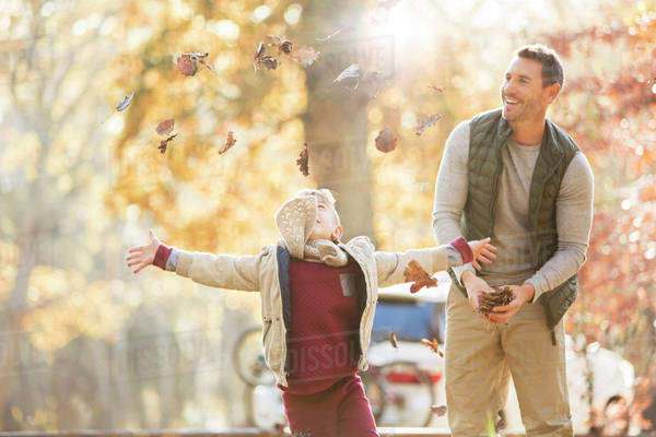 Father and son throwing autumn leaves overhead Royalty-free stock photo