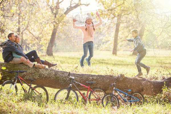Family playing on fallen log in autumn woods Royalty-free stock photo