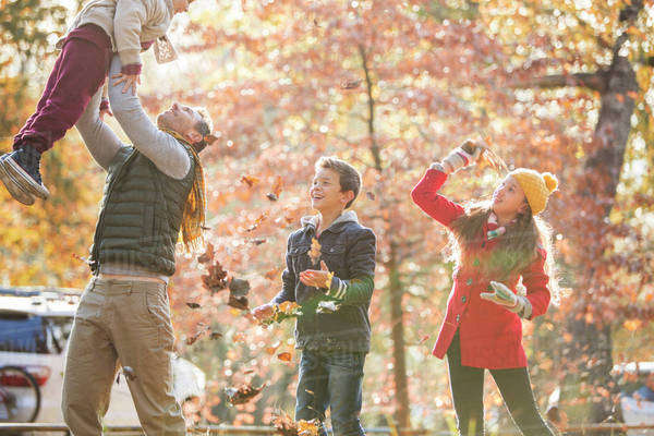 Playful father and children playing in autumn leaves Royalty-free stock photo