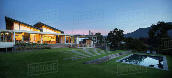 Illuminated modern house beyond yard and swimming pool at night Royalty-free stock photo