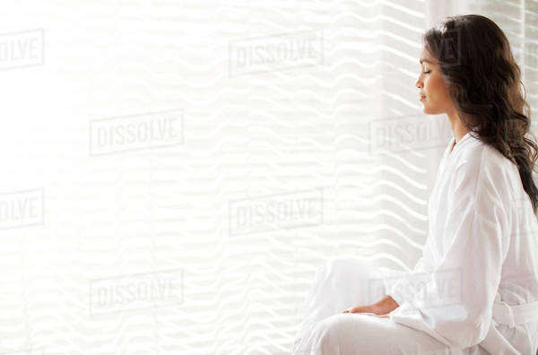 Serene woman in bathrobe meditating at sunny window Royalty-free stock photo