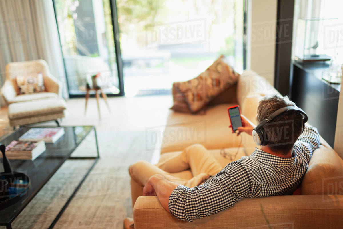 Man with headphones and mp3 player listening to music, relaxing on sofa Royalty-free stock photo