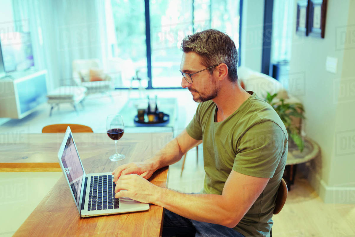 Man working from home at laptop, drinking red wine in kitchen Royalty-free stock photo