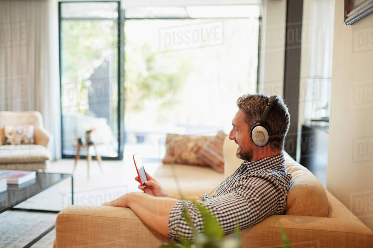 Man with headphones and mp3 player listening to music at home Royalty-free stock photo