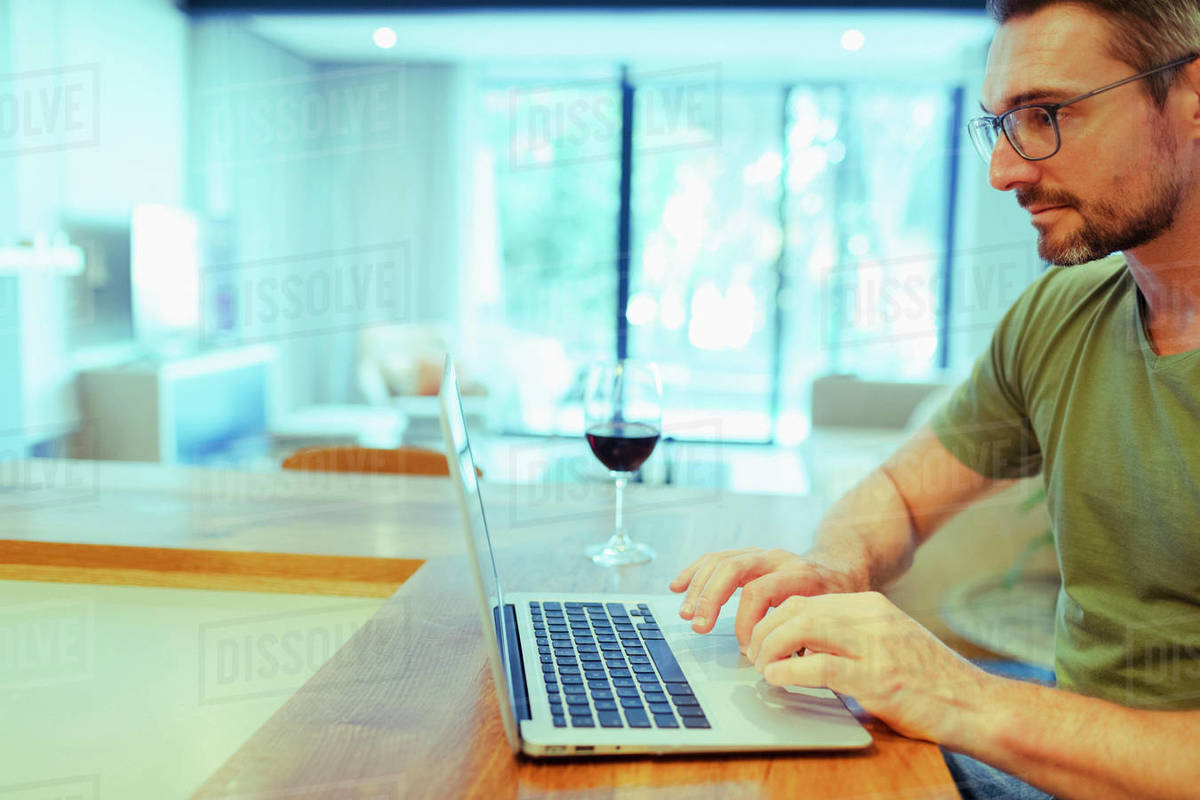Man using laptop and drinking wine, working from home in kitchen Royalty-free stock photo