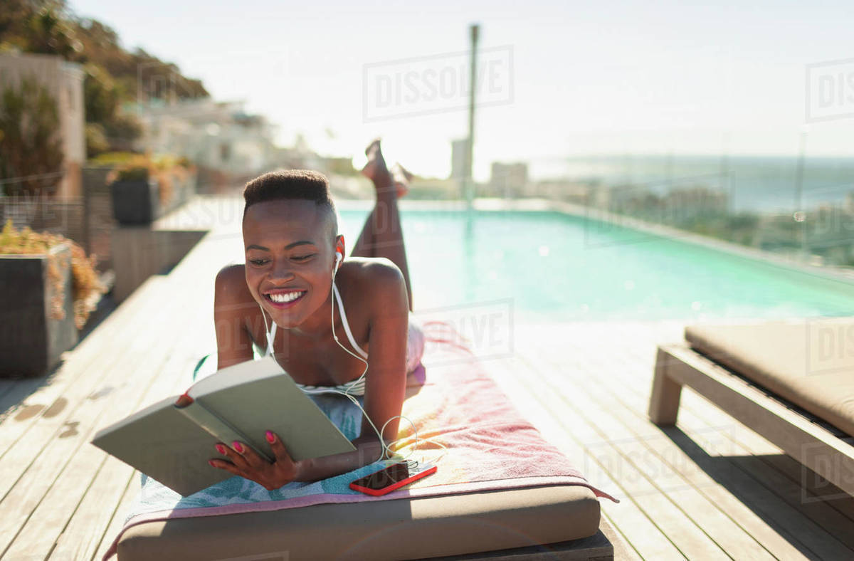 Smiling, carefree young woman reading book at sunny poolside Royalty-free stock photo