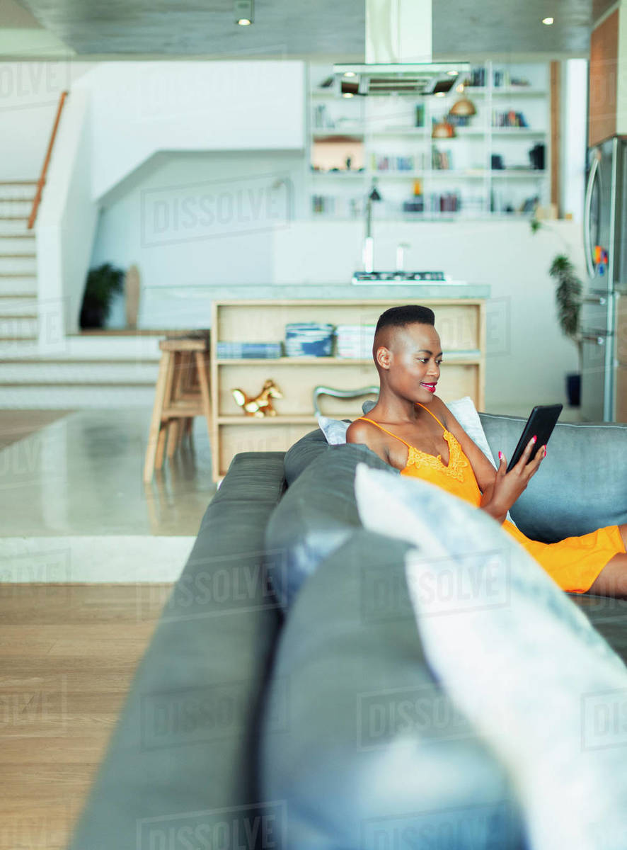 Young woman using digital tablet on living room sofa Royalty-free stock photo