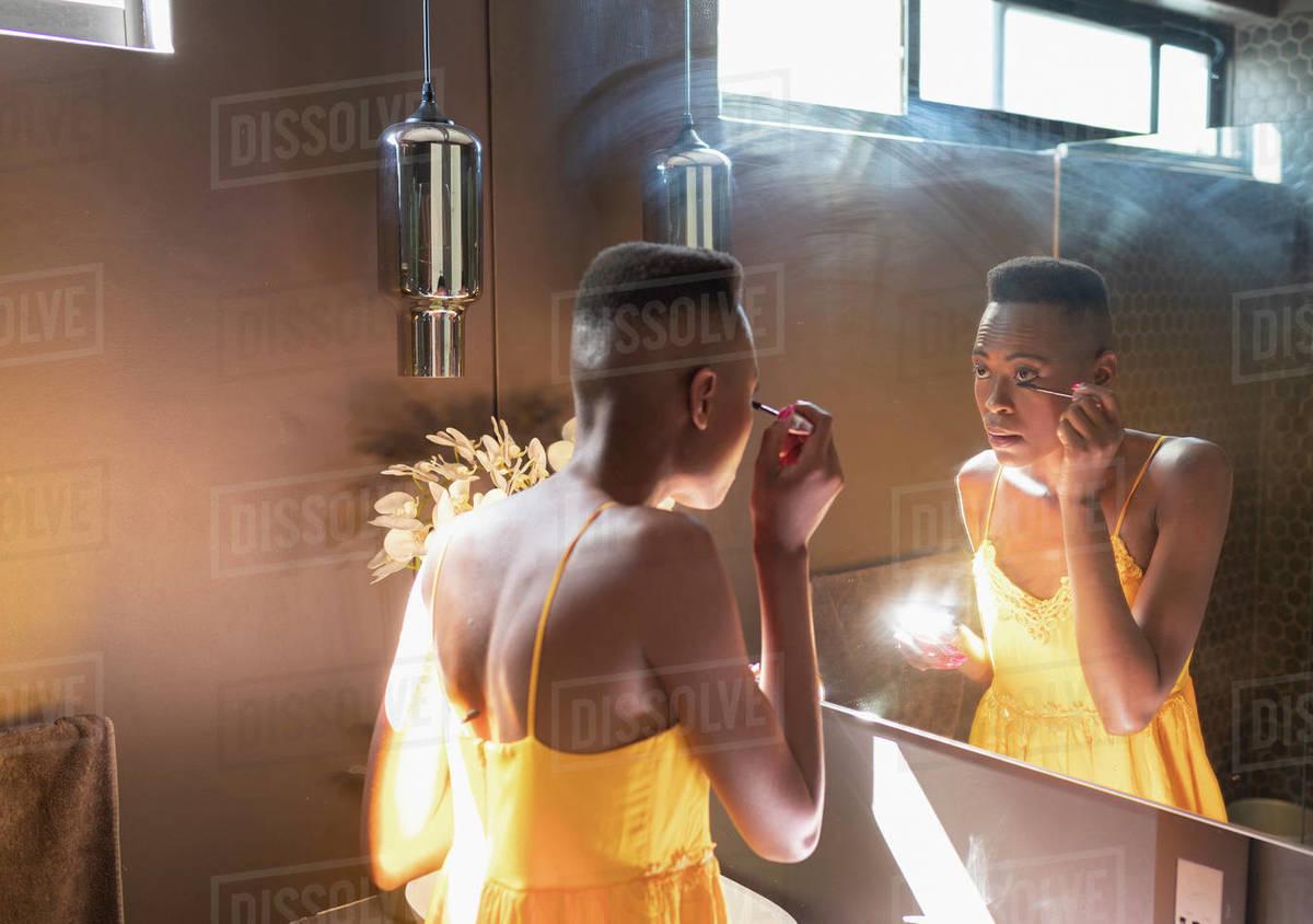 Young woman applying mascara in sunny bathroom mirror Royalty-free stock photo