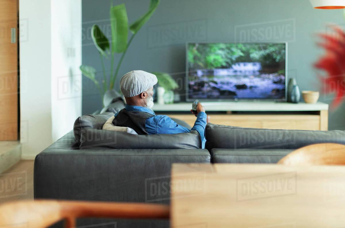 Man watching TV on living room sofa Royalty-free stock photo
