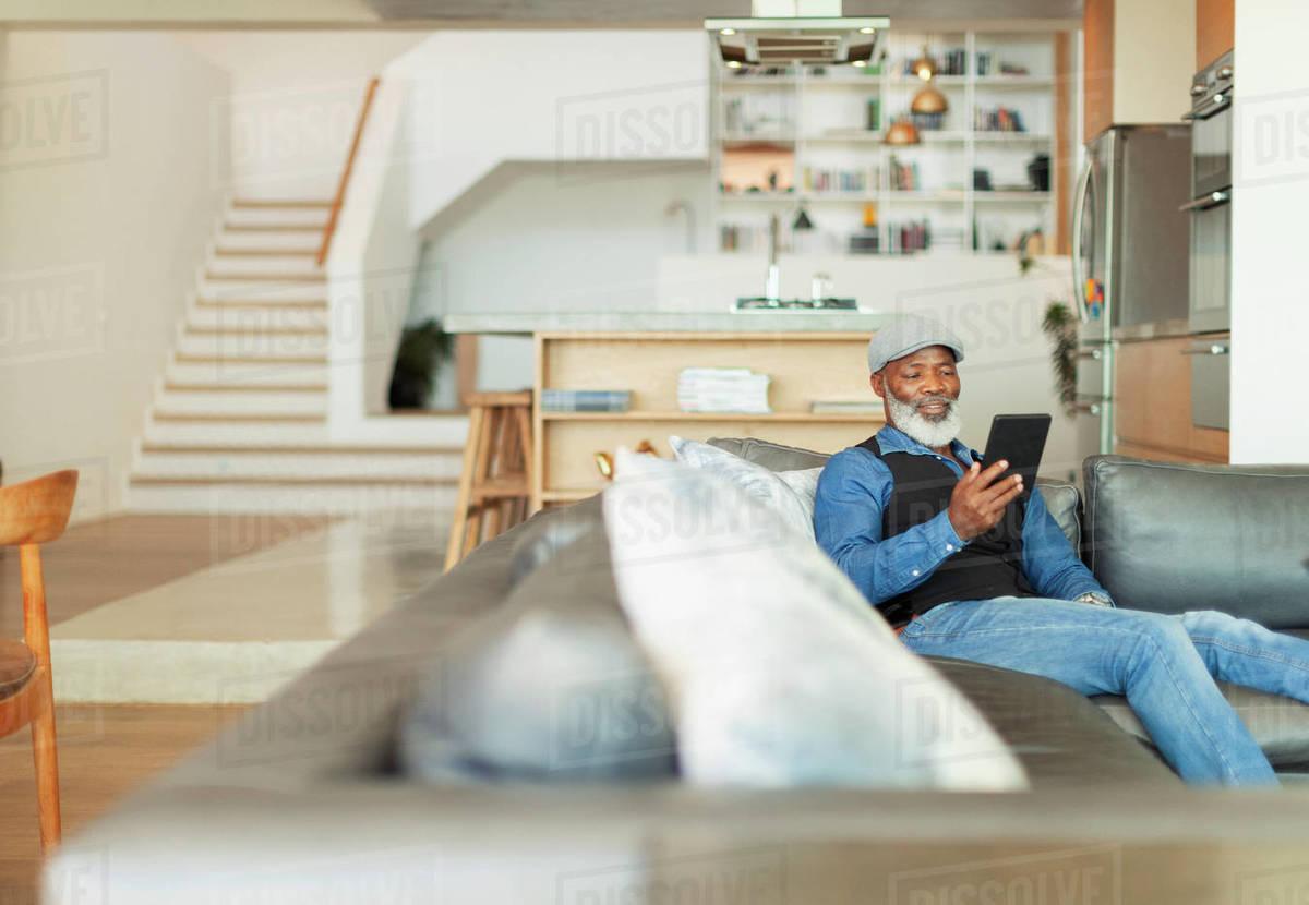 Man using digital tablet on living room sofa Royalty-free stock photo