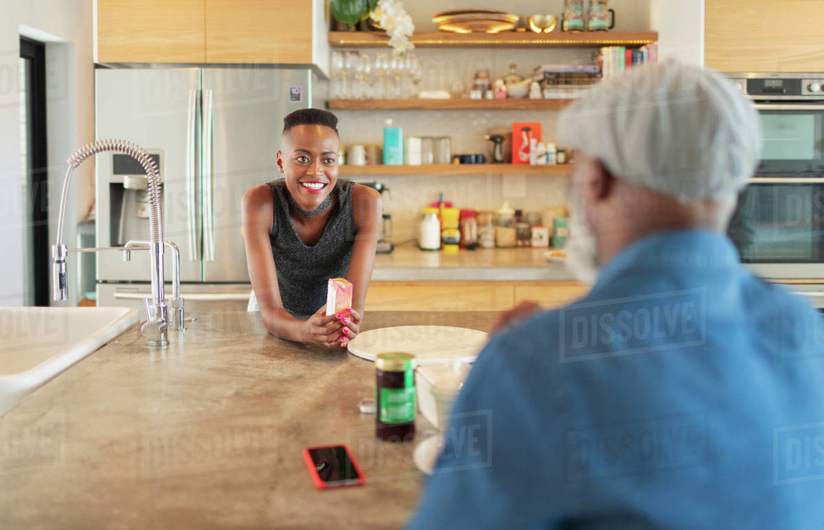 Father and daughter talking, enjoying breakfast in kitchen Royalty-free stock photo