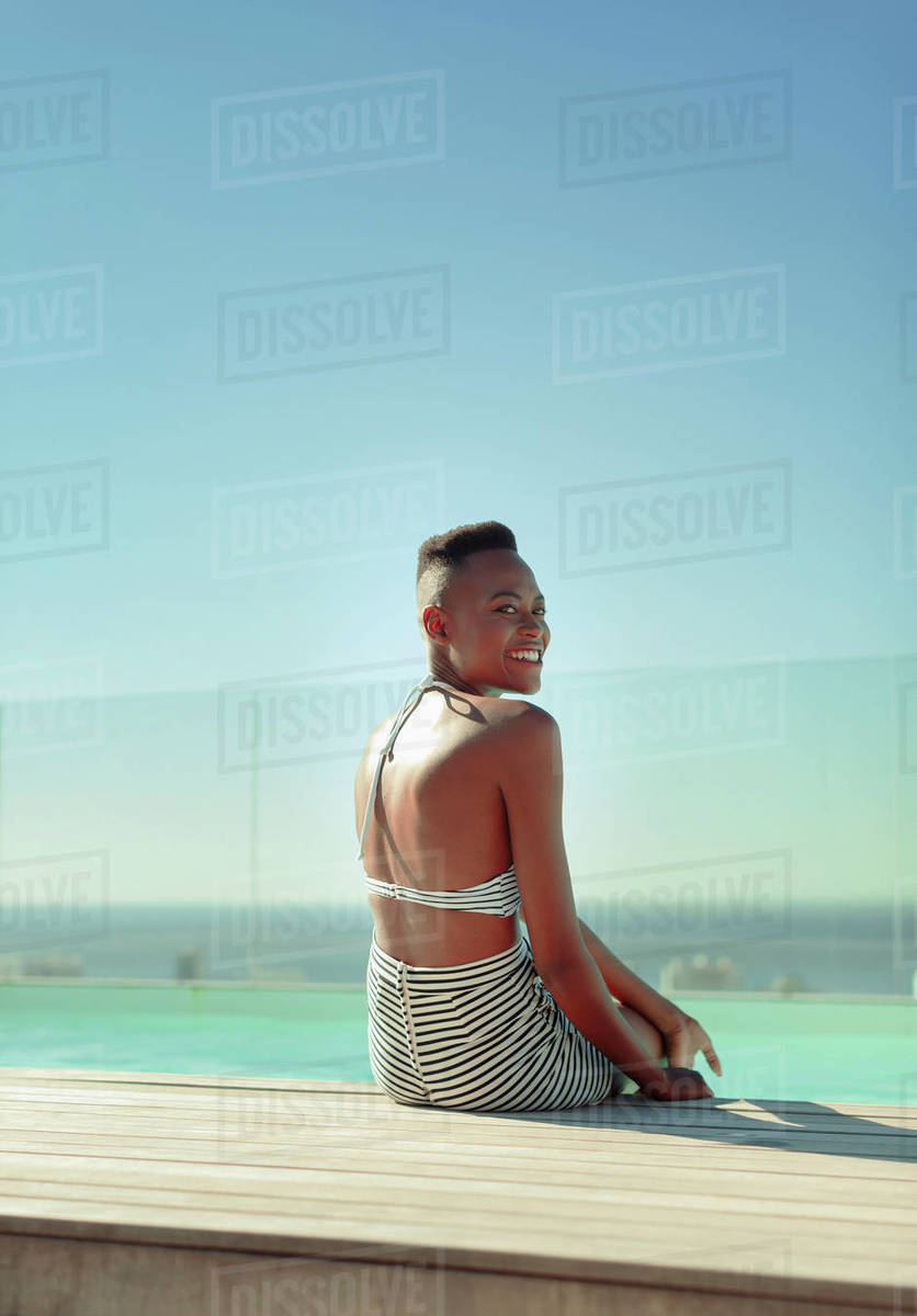Portrait smiling, carefree young woman at sunny poolside Royalty-free stock photo