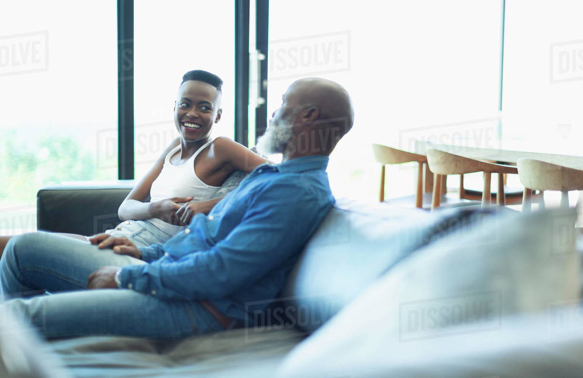 Father and daughter talking on living room sofa Royalty-free stock photo