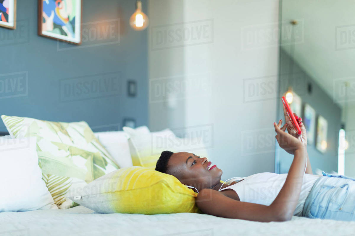 Young woman relaxing on bed, listening to music with headphones and mp3 player Royalty-free stock photo