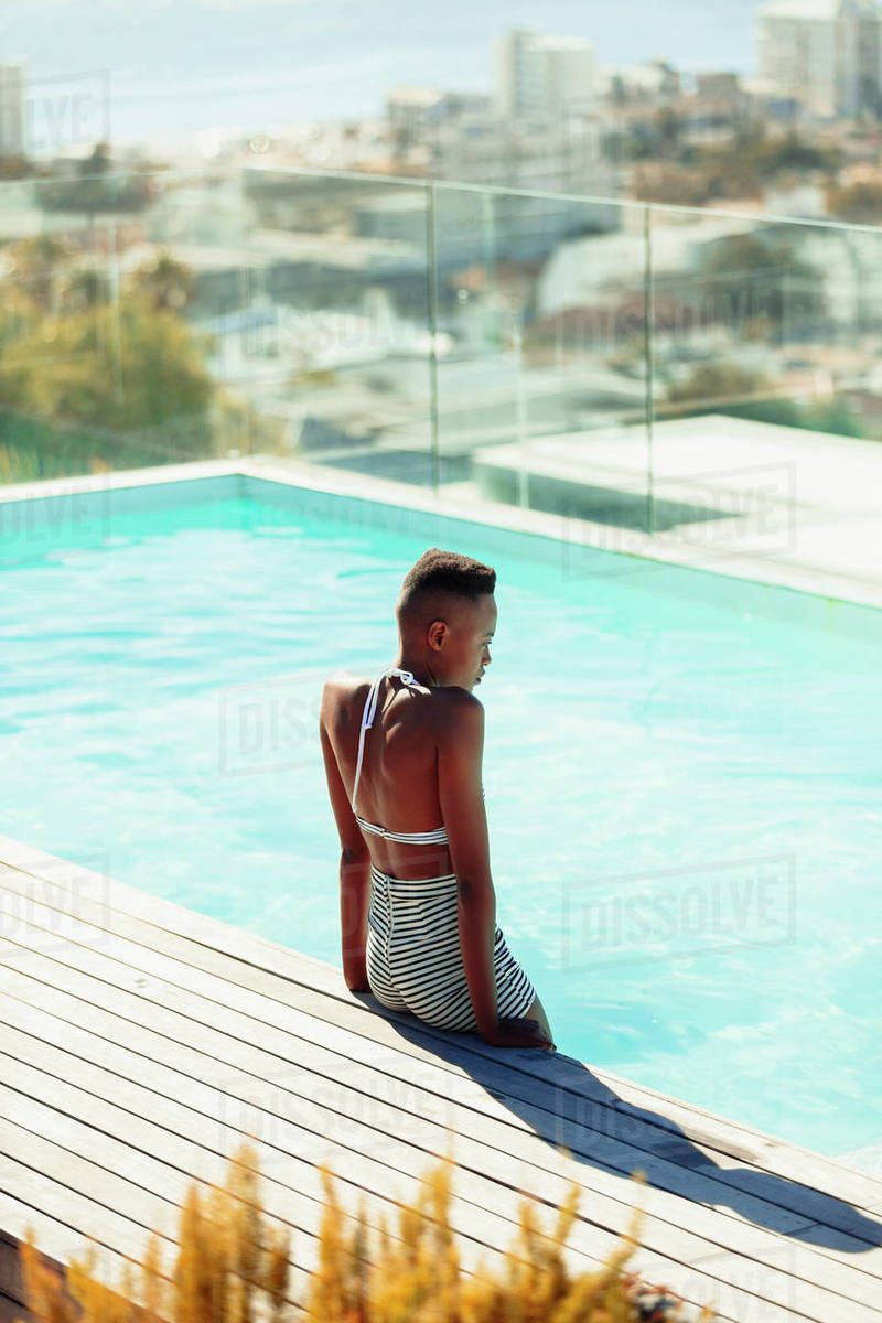 Serene young woman at sunny rooftop swimming pool Royalty-free stock photo
