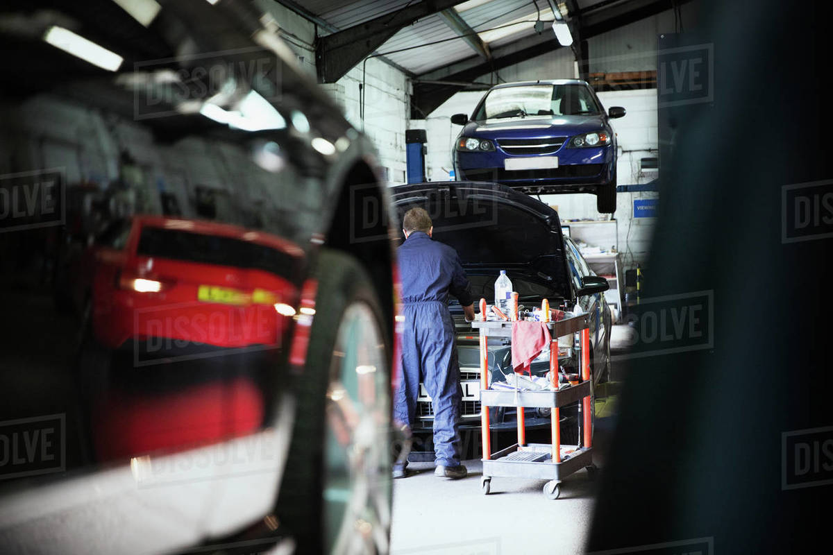 Male mechanic working under automobile hood in auto repair shop Royalty-free stock photo