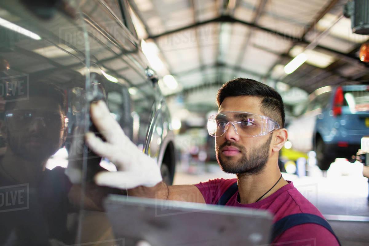 Focused male mechanic using digital tablet in auto repair shop Royalty-free stock photo