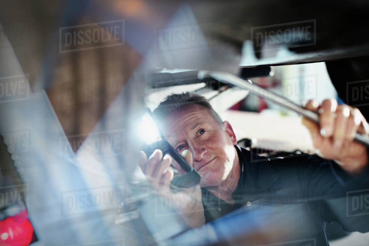 Male mechanic with flashlight working under car in auto repair shop Royalty-free stock photo