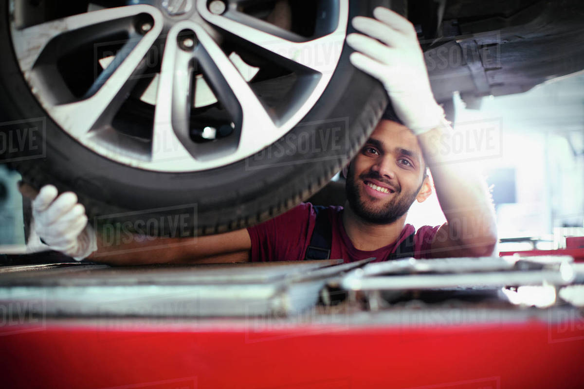 Portrait confident, smiling male mechanic working under car in auto repair shop Royalty-free stock photo