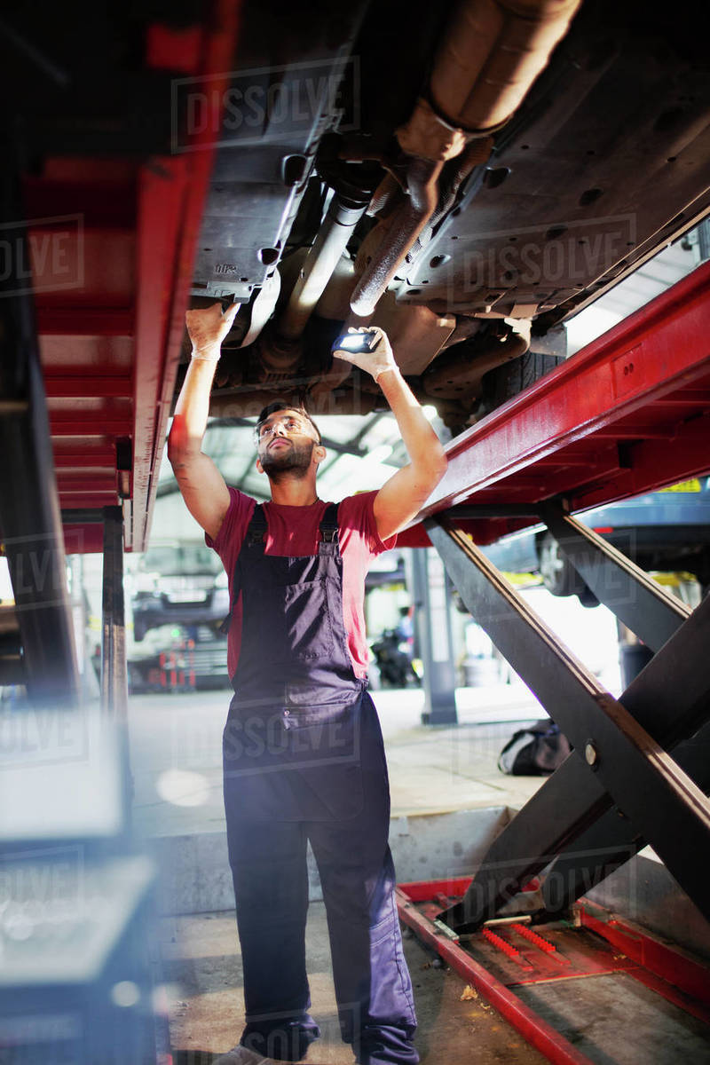 Male mechanic working under car in auto repair shop Royalty-free stock photo