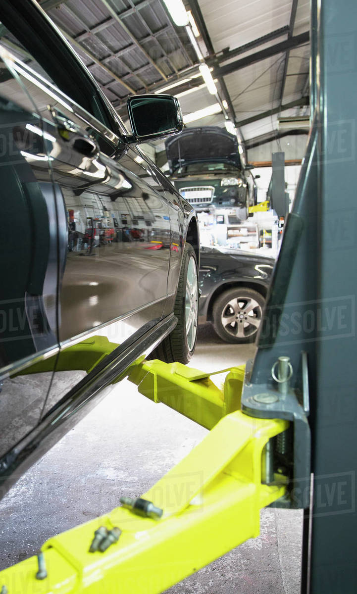 Car on hydraulic lift in auto repair shop Royalty-free stock photo