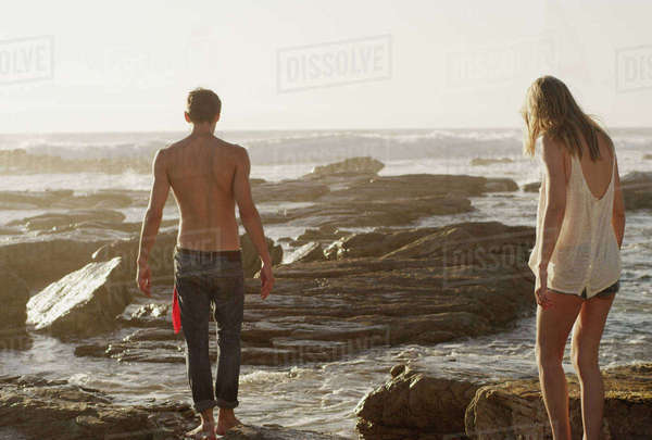 Young couple walking on rocks at ocean Royalty-free stock photo