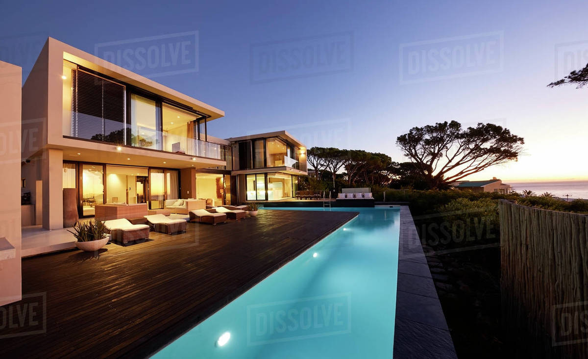 Modern luxury home showcase deck and swimming pool at sunset stock photo