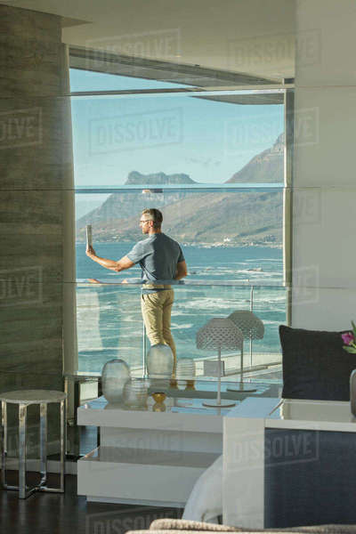 Reflection of man using digital tablet camera on luxury balcony with ocean view Royalty-free stock photo