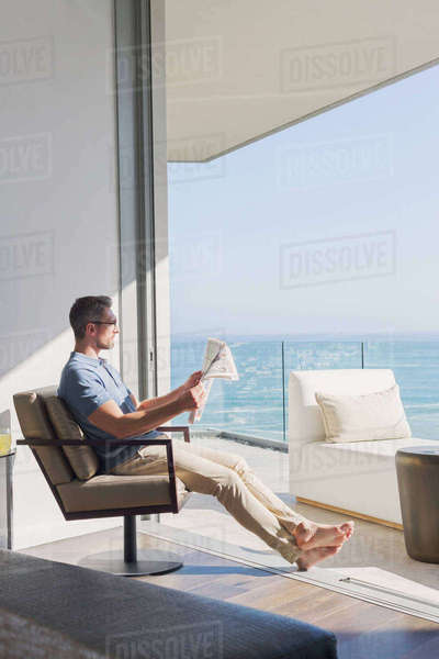 Man relaxing reading newspaper in sunny patio doorway with ocean view Royalty-free stock photo