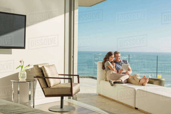 Couple using digital tablet on chaise lounge on sunny luxury balcony with ocean view Royalty-free stock photo