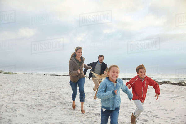 Playful family running on winter beach Royalty-free stock photo