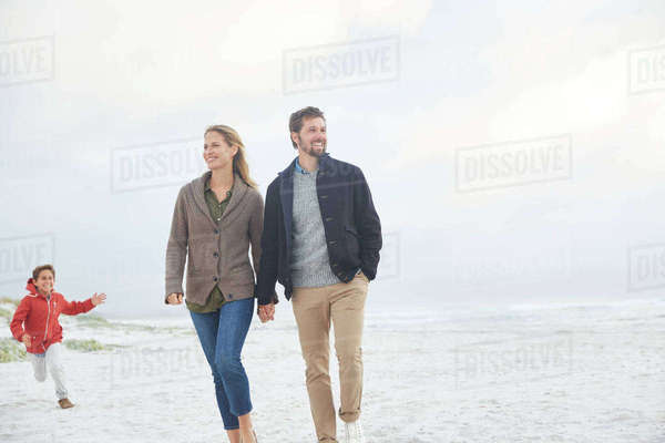 Family walking and running on winter beach Royalty-free stock photo
